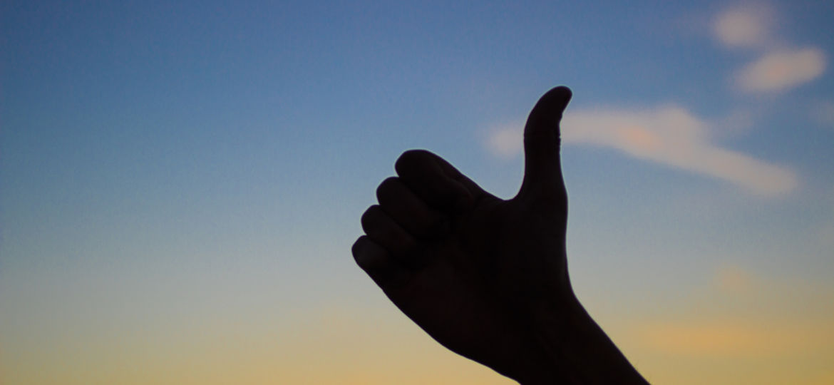 Silhouette of hand with thumbs up, symbol of like, satisfaction and agreement, sky background