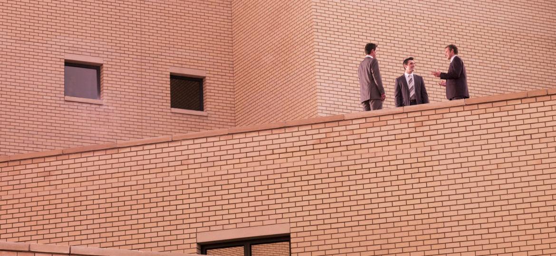 Businessmen meeting on brick building