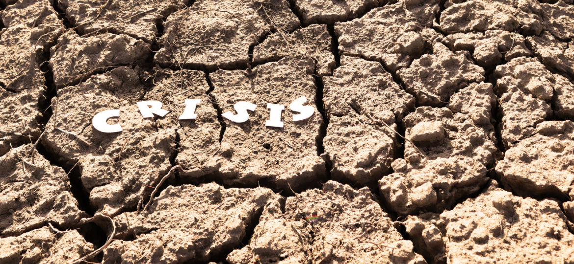 The word CRISIS in paper letters on the background of dry earth with cracks. Crisis concept. Banner.