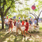 A senior couple with extended family dancing on a garden party or family celebration outside in the backyard.